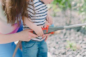 kleiner Junge mit Gartenschlauch