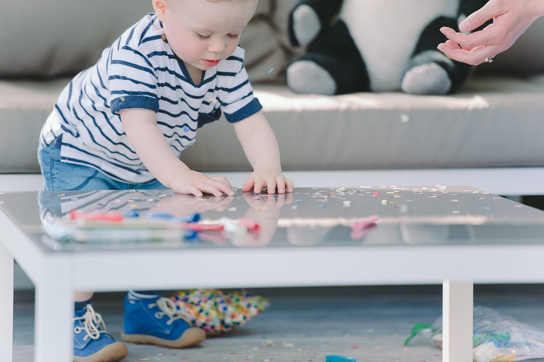 Junge spielt mit Konfetti auf dem Tisch