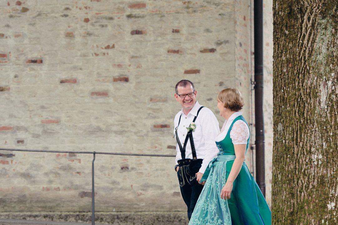 Glückliches Brautpaar in Hochzeitsdirndl und Festtagslederhose