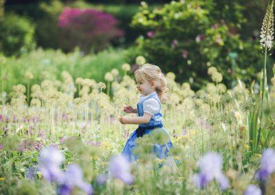 Kinderfoto kleines Mädchen in blauem Dirndl im Botanischen Garten Augsburg