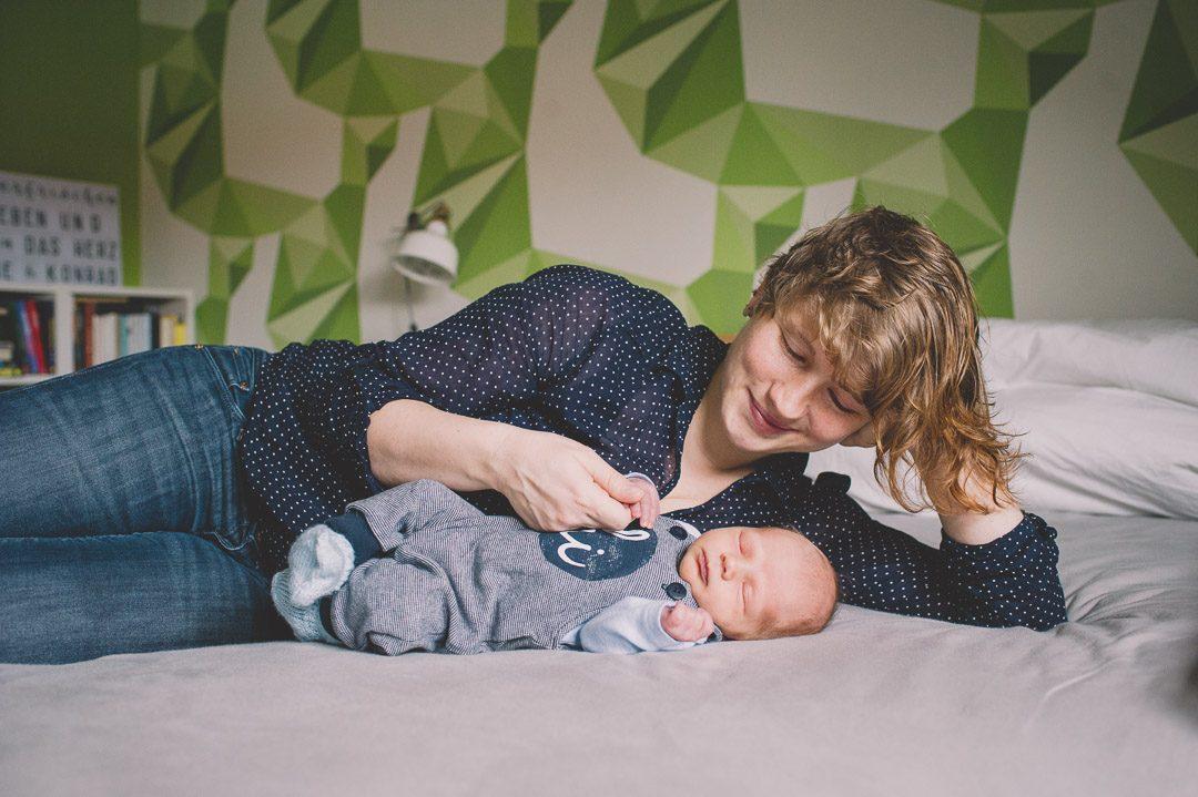 Baby schläft neben Mutter im Bett während Fotoshooting