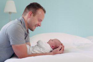 Vater mit Baby Sohn im hellblauen Schlafzimmer für Babyfotos