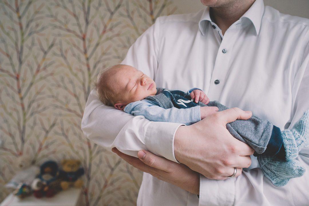 Vater hält neigeborenen Sohn im Arm