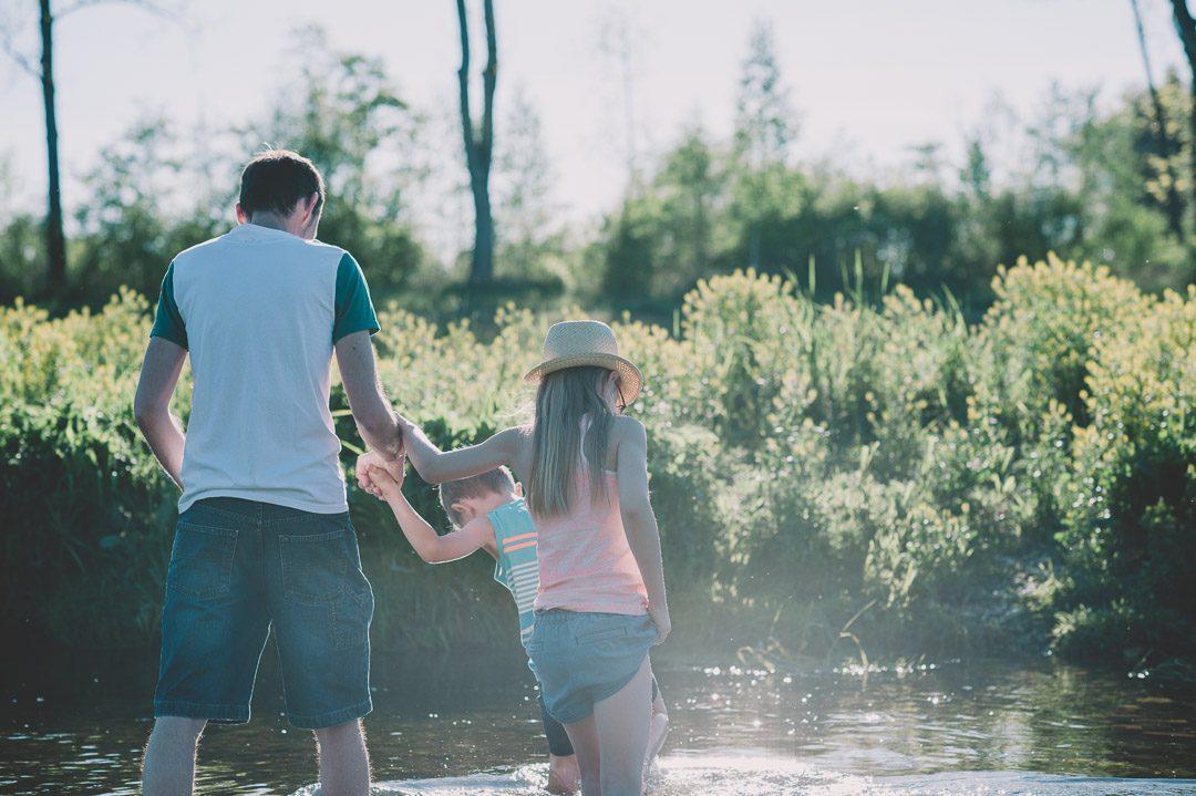 Vater und Kinder laufen in der Wertach