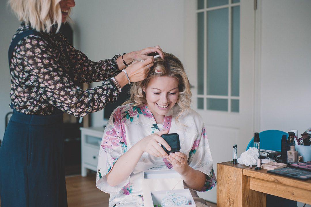 Braut öffnet Geschenk während Getting Ready