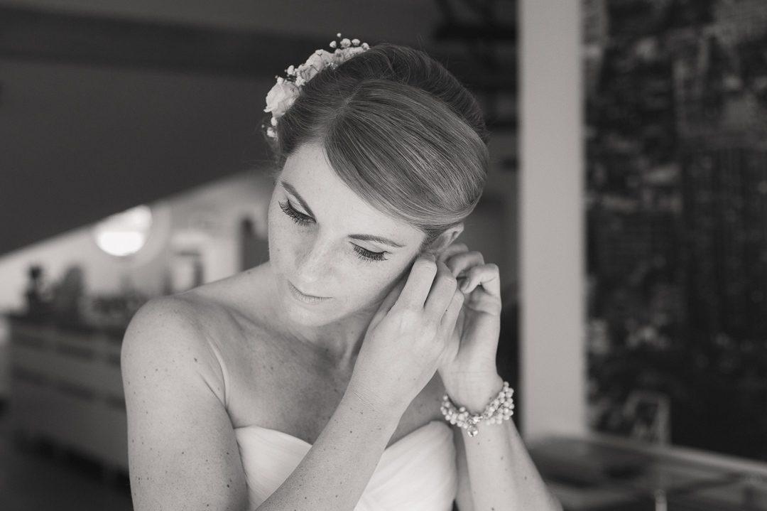 Braut legt Perlenohrringe an