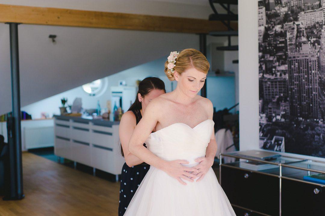 Brautjungfer schließt Hochzeitskleid der Braut Augsburg