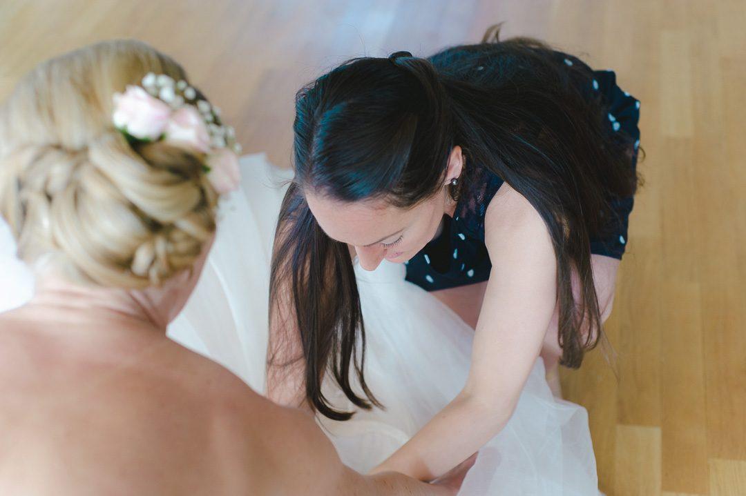 Trauzeigin hilft Braut beim Anziehen von Chimmy Choo Sandalen