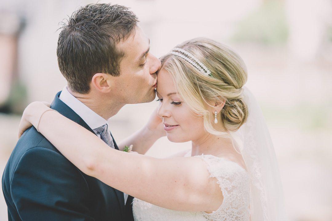 Liebevoller Bräutigam während Paarportraits zur Hochzeit