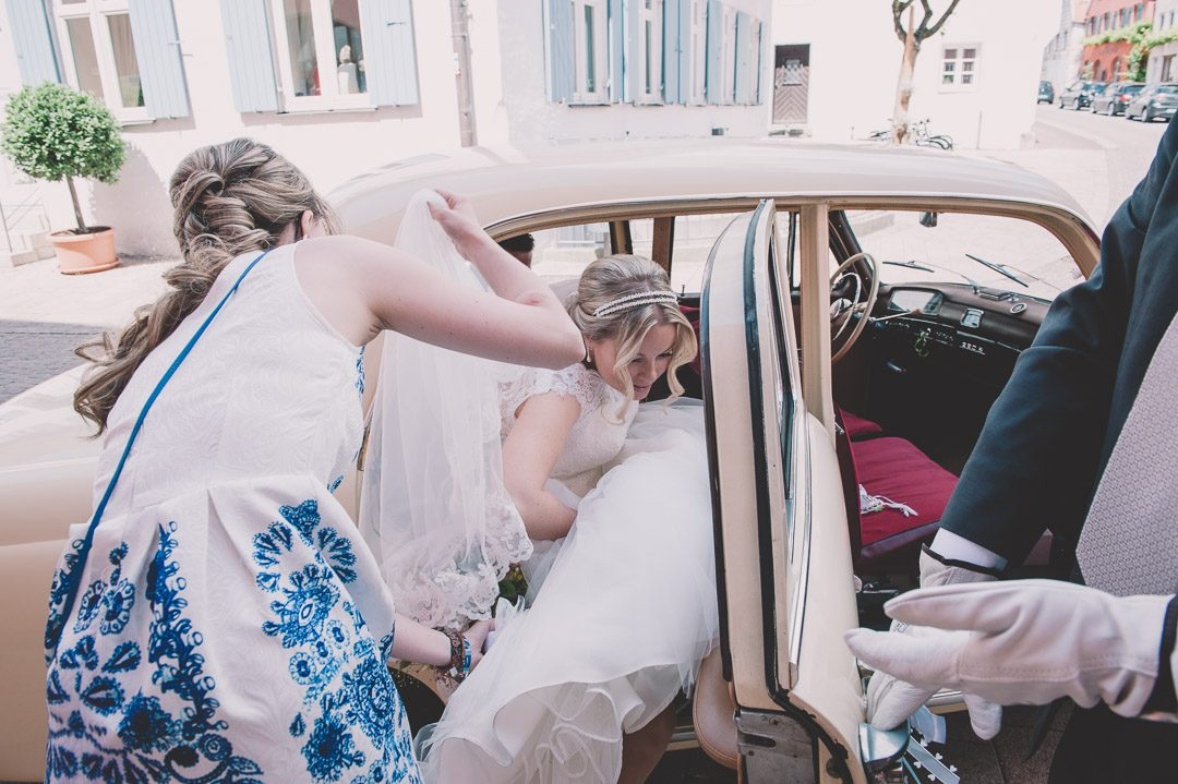 Braut mit langem weißen Kleid steigt ins Brautauto