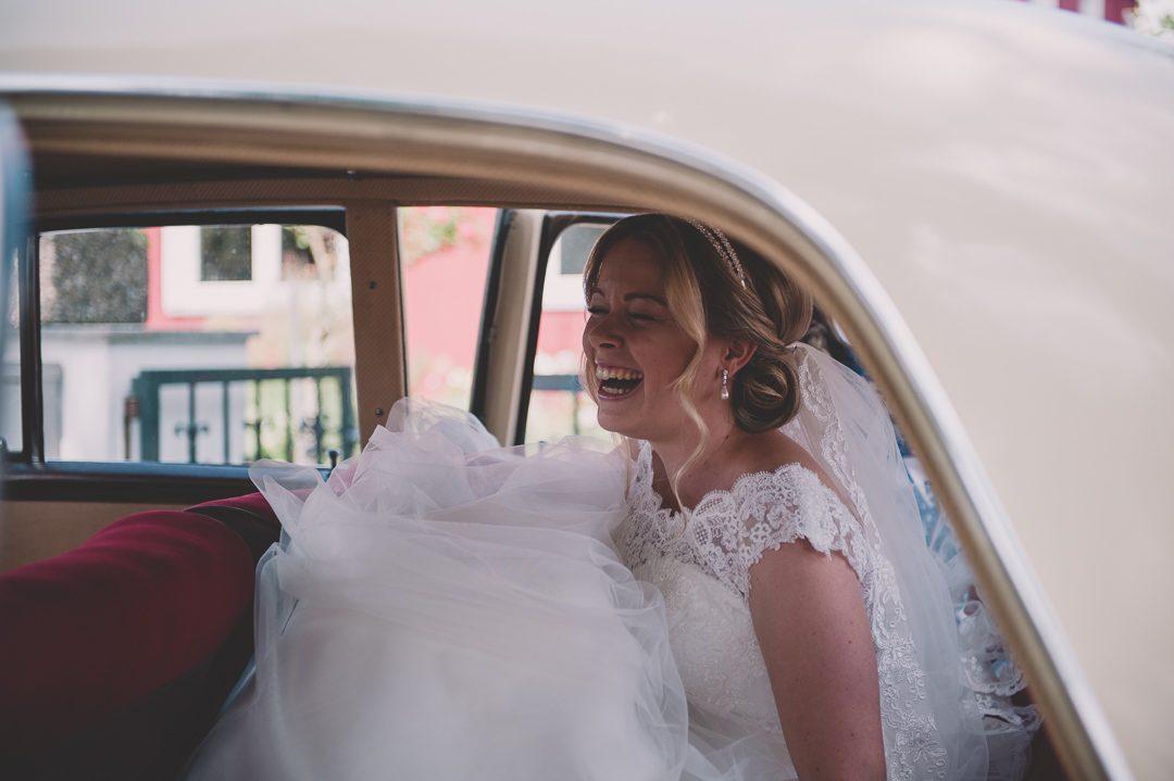 Lachende Braut in Oldtimer Mercedes Brautauto