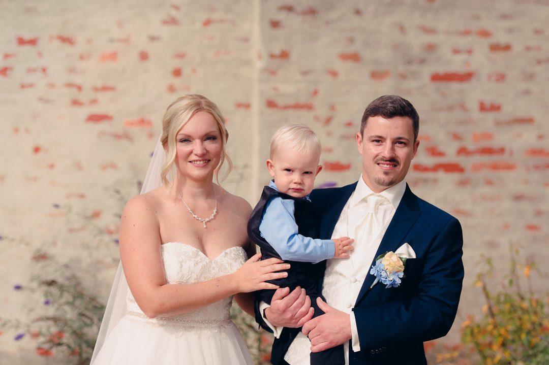 Braut und Bräutigam mit Sohn bei Hochzeitsfotos