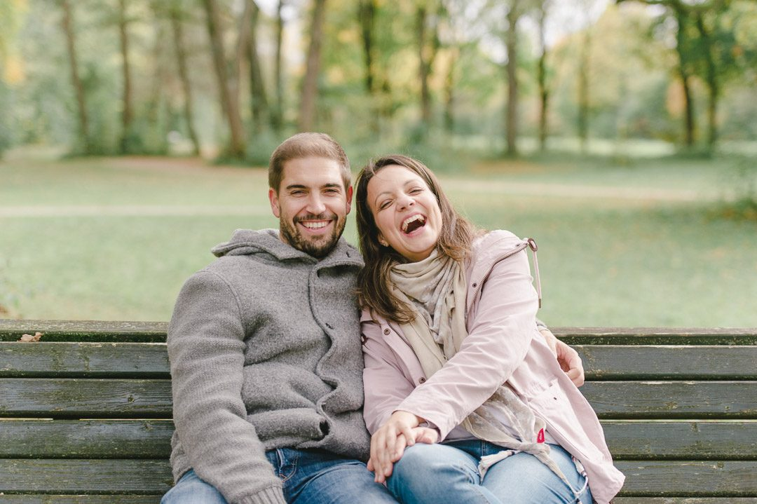Junge Eltern lachend auf einer Bank