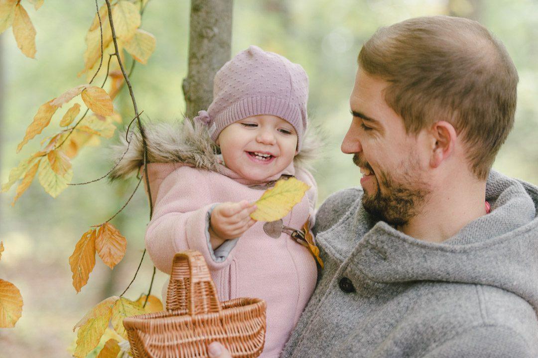 Papa und Kleinkind sammeln bunte Blätter
