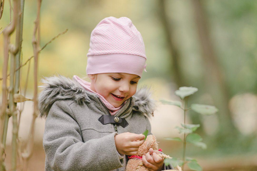 Kleines Mädchen freut sich über Herbstlaub