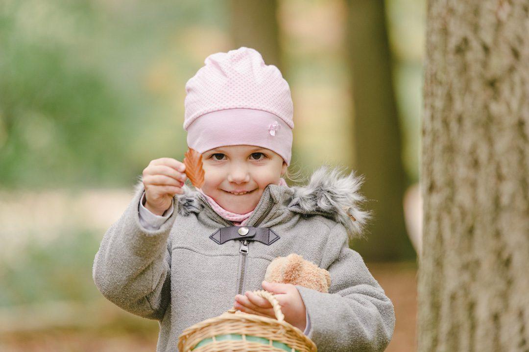 Mädchen sammelt bunte Herbstblätter mit Korb