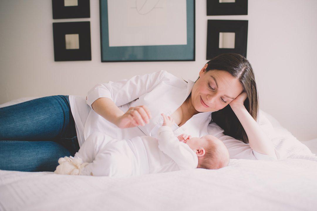 Mutter spielt mit Baby Tochter auf dem Bett