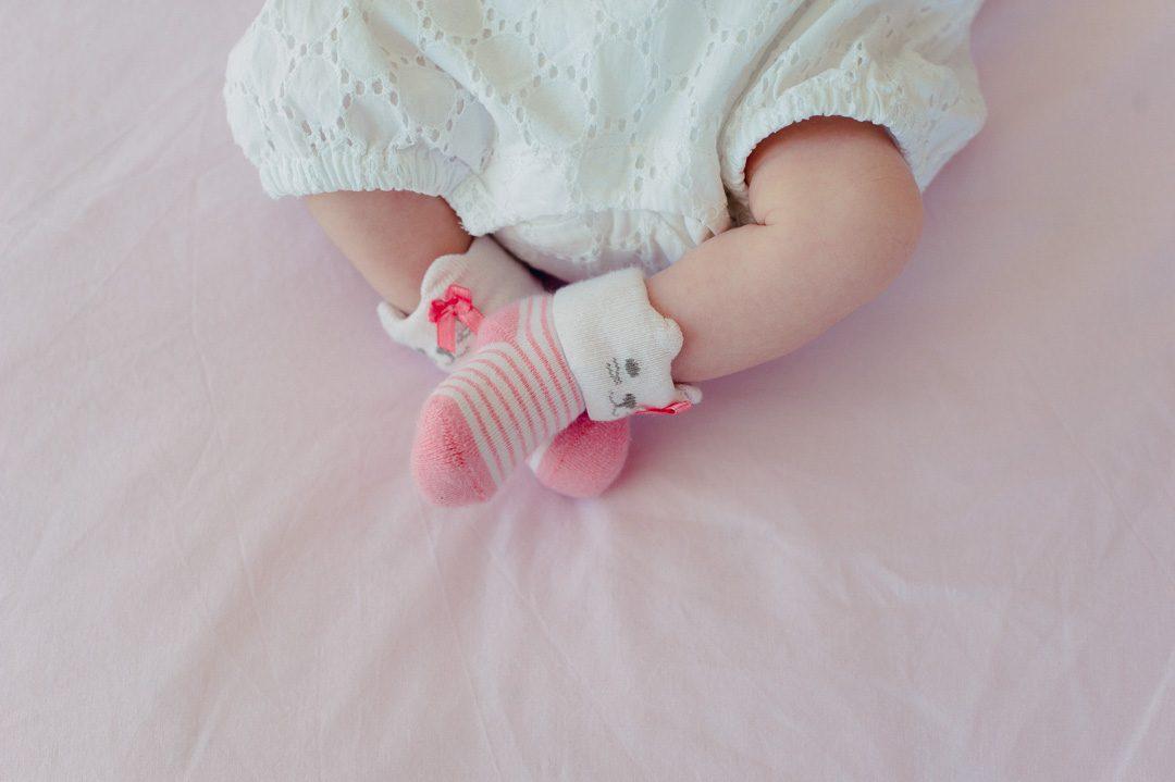 Baby gilr mit rosa Socken und Teddy