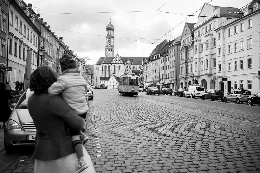 Braut mit Kind wartet auf historische Straßenbahn in Augsburg