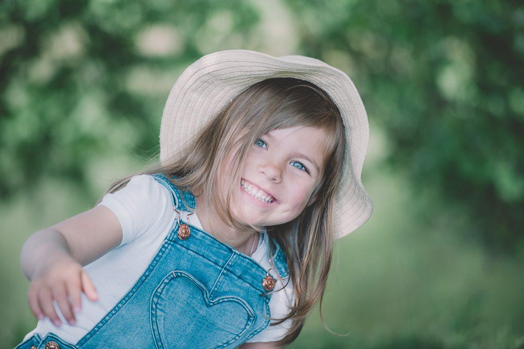 Lachendes Mädchen mit Strohhut bei Kinderbildern mit Kinderfotograf Petsy Fink in Aichach