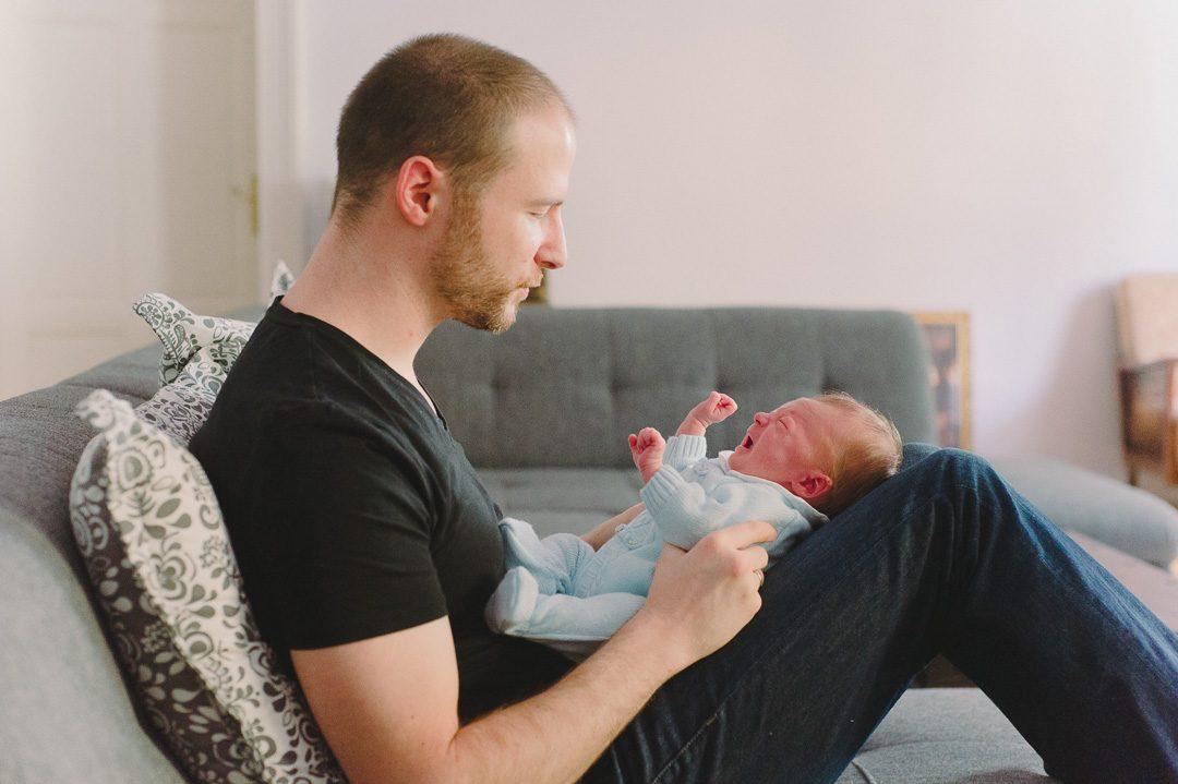 Papa mit neugeborenem Sohn zuhause auf der Couch in Augsburg