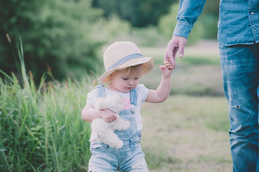 Kleines Mädchen mit Strohhut an Papas Hand
