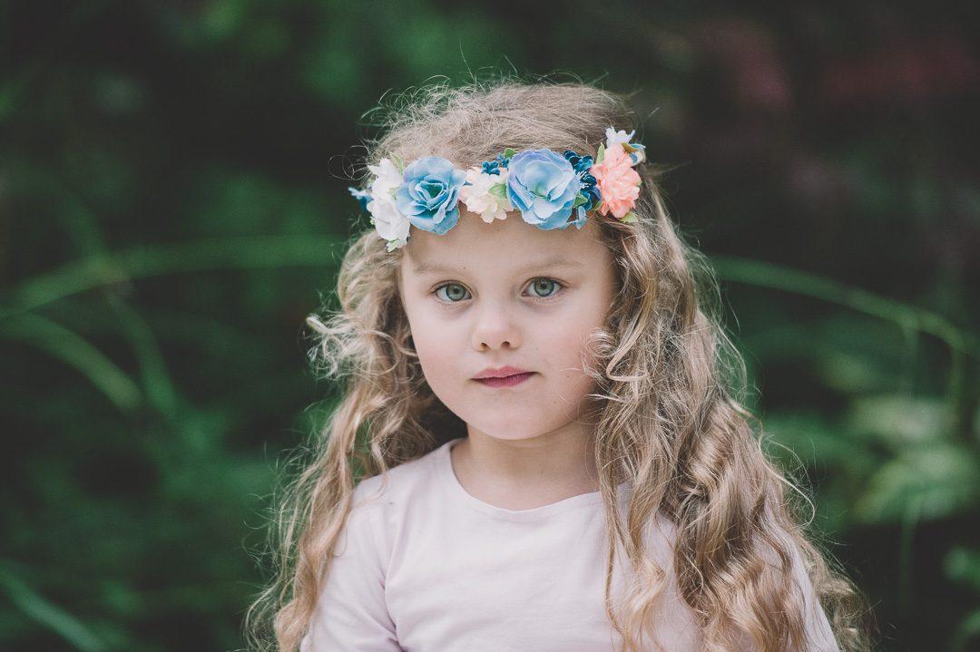 Kinderfoto von Mädchen mit lnagen Haaren und Blumenkranz