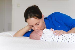 Junge Mama kuschelt mit ihrem kleinen Baby Sohn