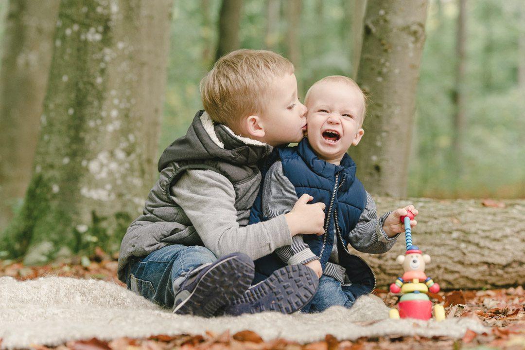 Zwei Brüder spielen während Familienfotos in Augsburg