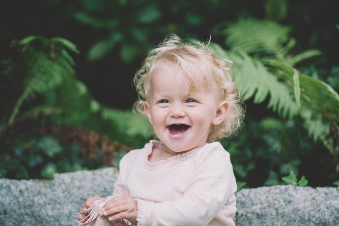 Lachendes Mädchen mit blonden Locken und blauen Augen
