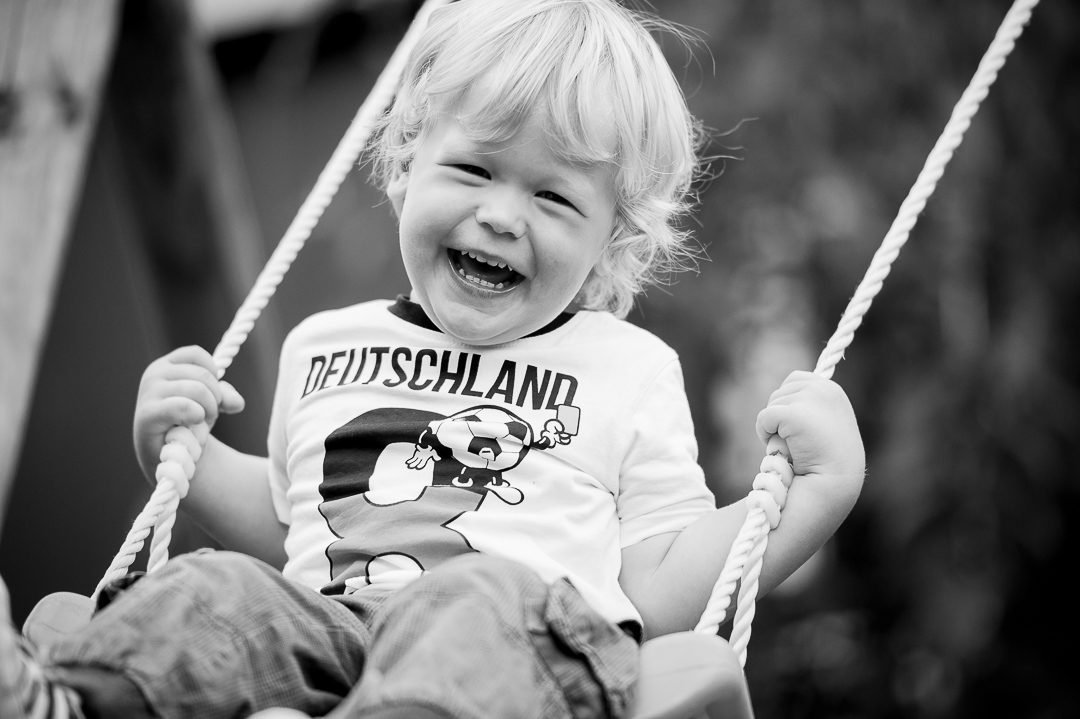 Lachender Junge auf Schaukel