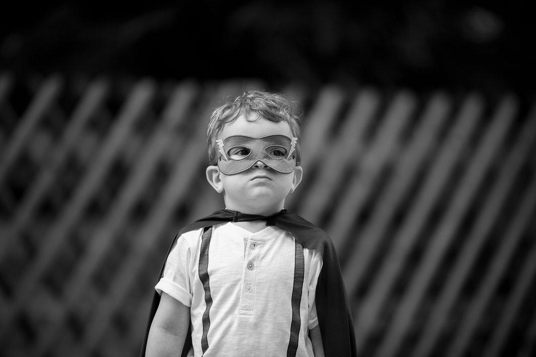 Kleiner Junge mit Batman Cape während Fotoshooting