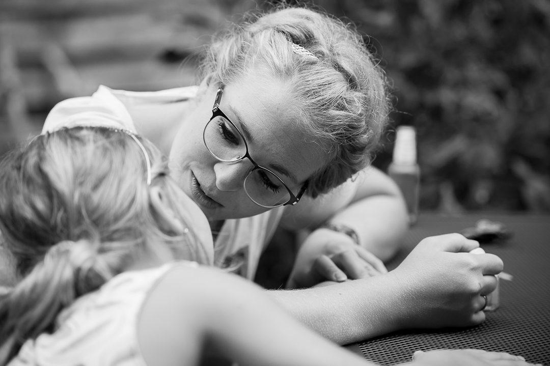 Mama trägt kleinem Mädchen Nagelack auf