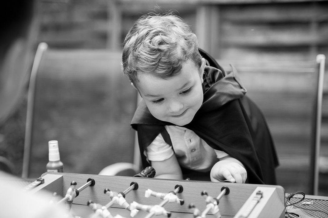 Junge in Batman Cape spielt Tischfußball
