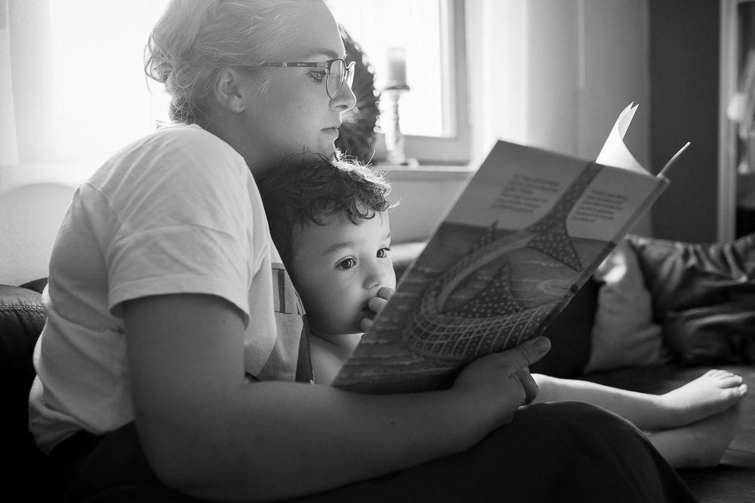 Mama und Sohn kuscheln beim Bilderbuch lesen