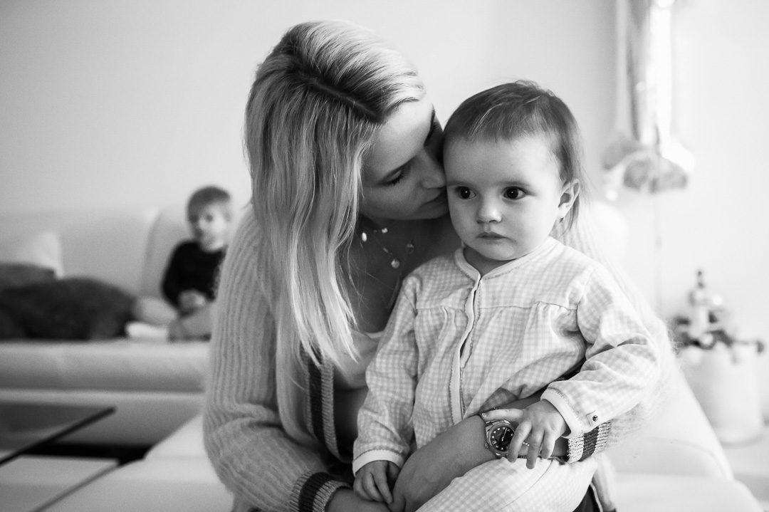 Mama kuschelt mit Tochter im Wohnzimmer