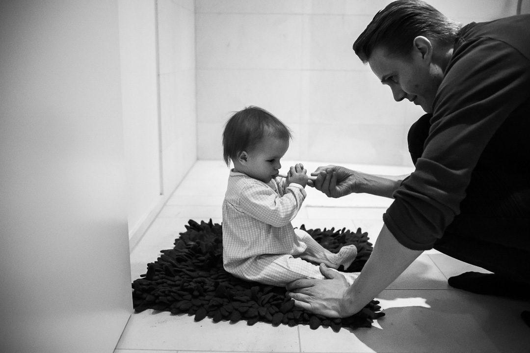 Papa hilft kleiner Tochter beim Zähneputzen