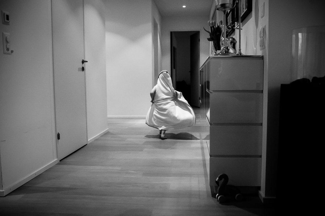 Kleiner Junge rennt mit Bademantel durch die Wohnung