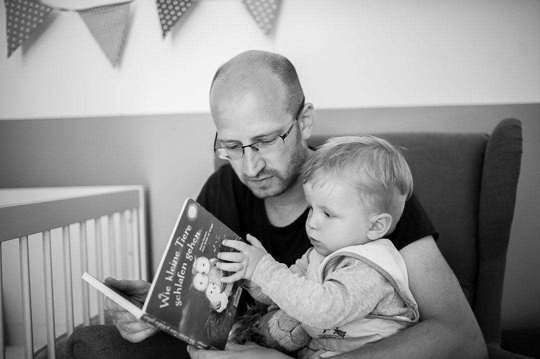 Vater und Sohn schauen Bilderbuch als Gute Nacht Geschichte an