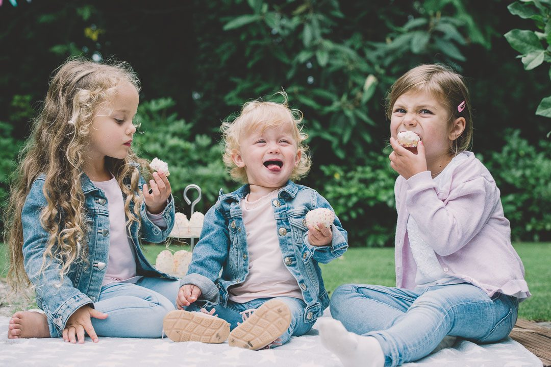 Kinder essen Mohrenköpfe im Garten