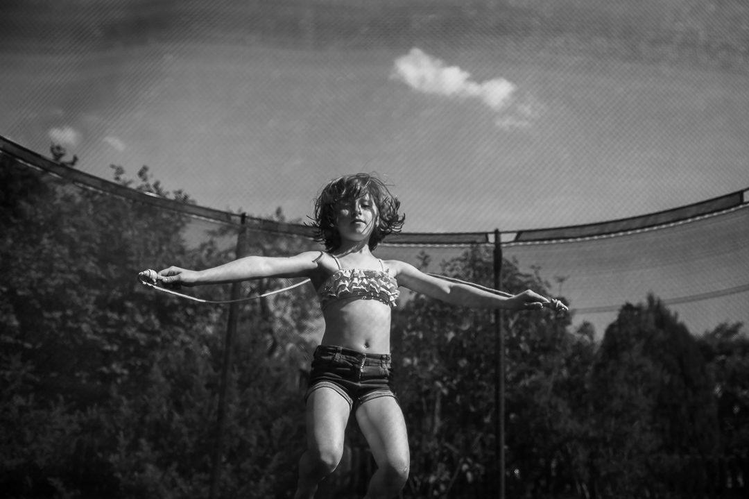 Junges Mädchen beim rope skipping im Trampolin