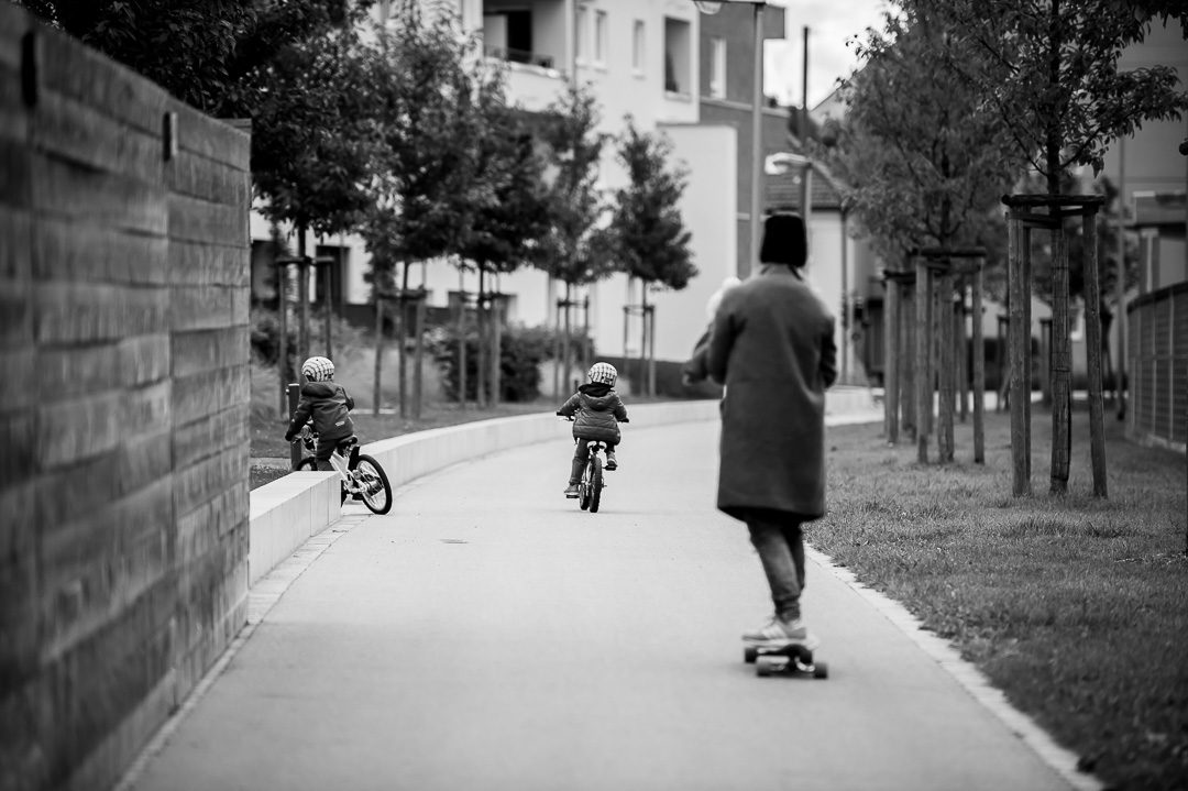 Mutter auf Skateboard mit Kindern auf Fahrrad beim Fotoshooting
