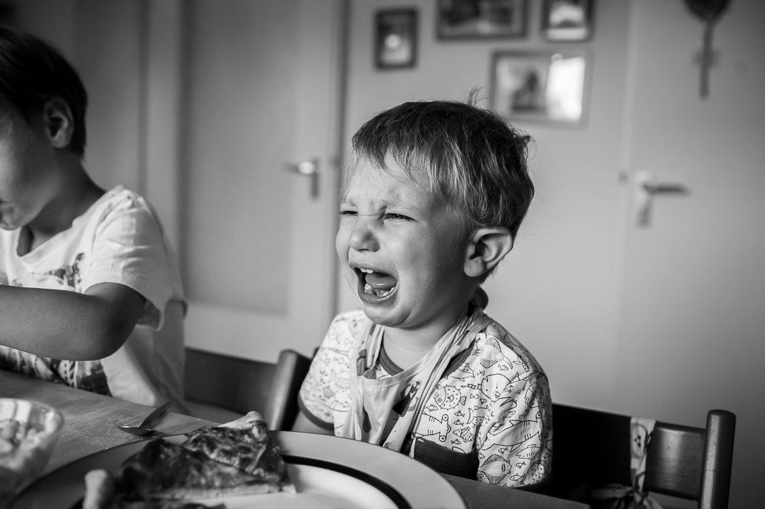 Junge weint beim Pizza Essen