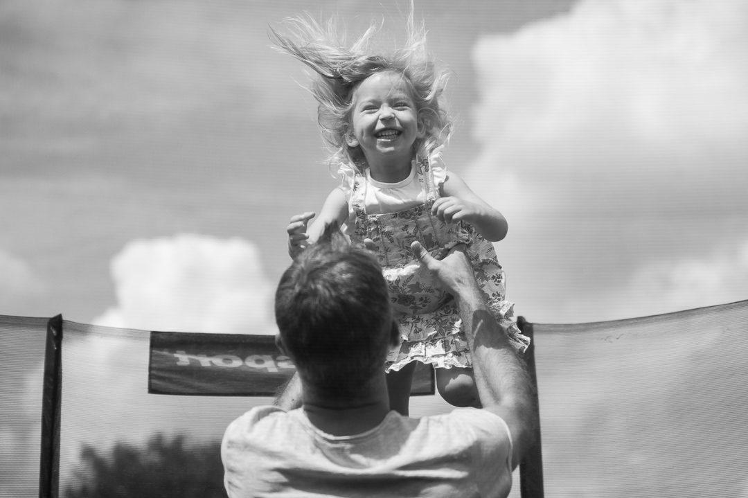 Vater und Tochter im Trampolin während Familienfotos