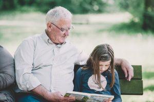 Opa und Enkelin lesen ein Buch