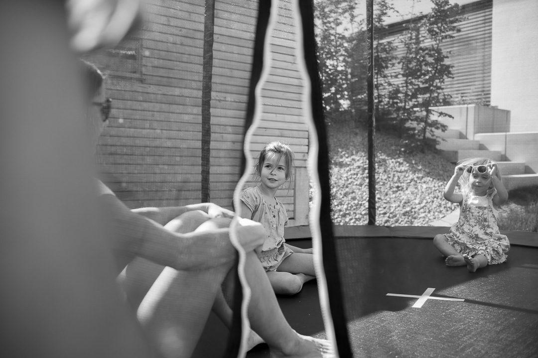 Mutter und Töchter im Trampolin hinter dem Haus