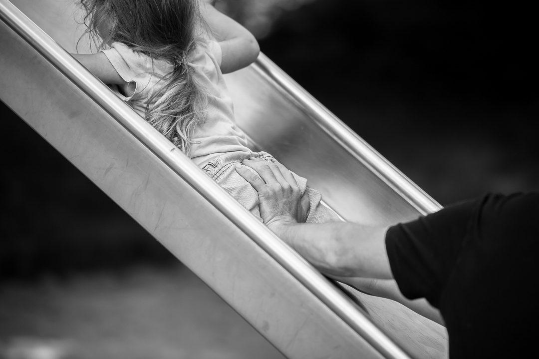 Papa hilft Tochter auf der Rutsche