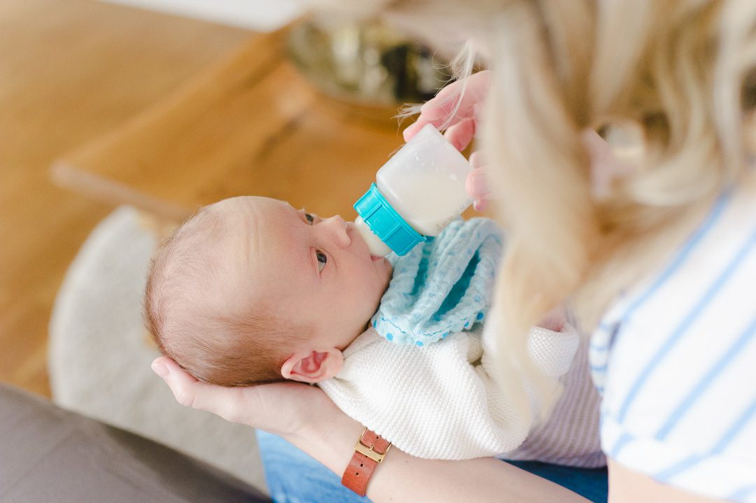 Baby trinkt die Flasche während Fotoshooting