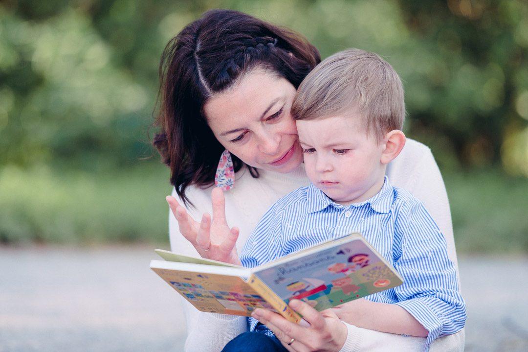 Mutter liest Kinderbuch während Familienfotos