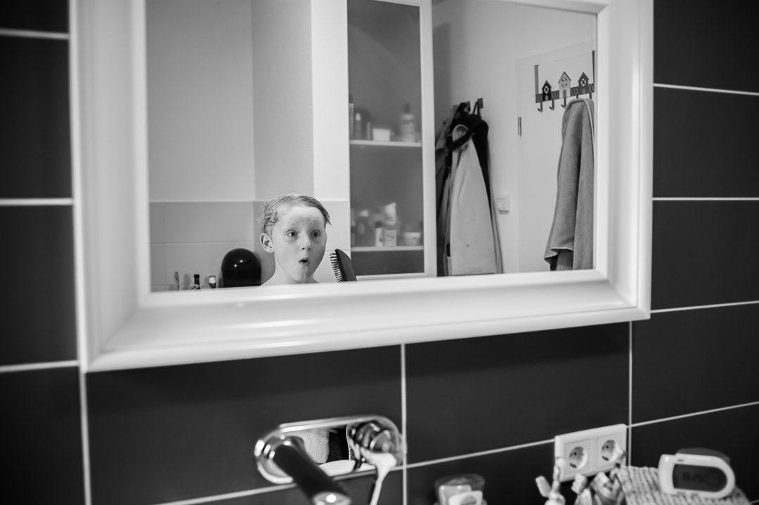 Junge macht Grimassen im Badezimmerspiegel